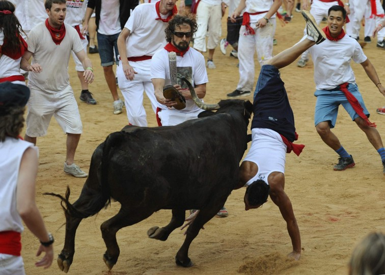 A fighting cow tosses a reveller at the bullring following the second running of the bulls of the San Fermin festival in Pamplona. Several runners suffered light injuries in a run that lasted two minutes and twenty five seconds, according to local media. (Eloy Alonso/Reuters photo)