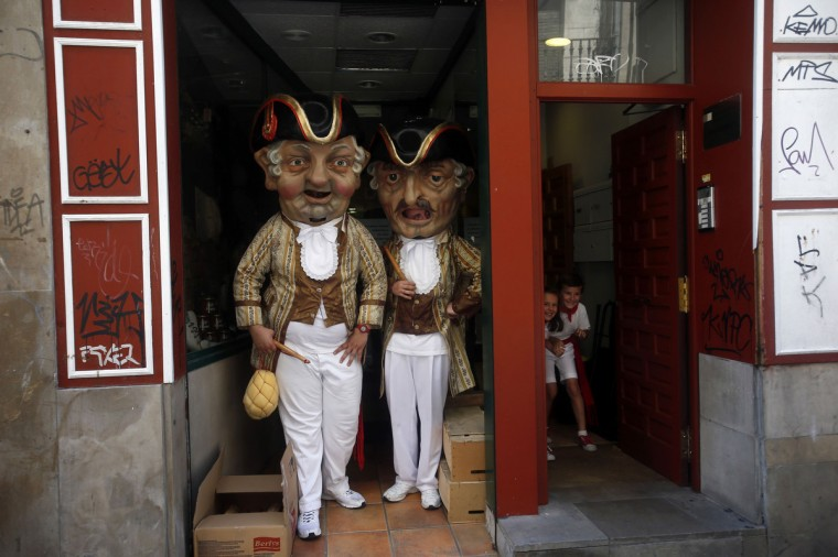 """""""Kilikis"""" wait for children to come out of the building where they were hiding during San Fermin festival's """"Comparsa de gigantes y cabezudos"""" (Parade of the giants and the big heads) in Pamplona. """"Kilikis"""", wearing outsized masks and playfully hitting bystanders with sponges on sticks, parade daily through the city accompanied by brass bands during the nine-day-long festival made popular by U.S. writer Ernest Hemingway. (Susana Vera/Reuters)"""