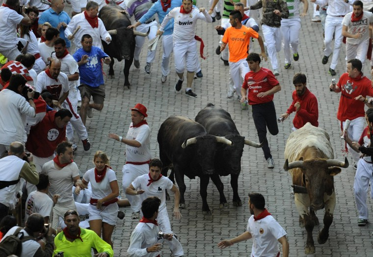 Runners sprint alongside Dolores Aguirre Ybarra fighting bulls at the entrance to the bull ring during the second running of the bulls of the San Fermin festival in Pamplona. (Eloy Alonso/Reuters photo)