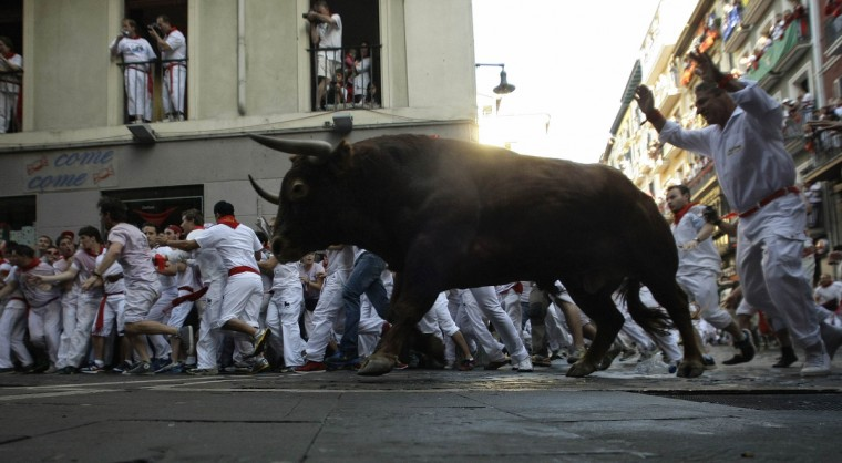 Runners sprint alongside Alcurrucen fighting bulls at the Estafeta corner during the first running of the bulls of the San Fermin festival in Pamplona. Several runners suffered light injuries in a run that lasted four minutes and six seconds, according to local media. (Eloy Alonso/Reuters photo)