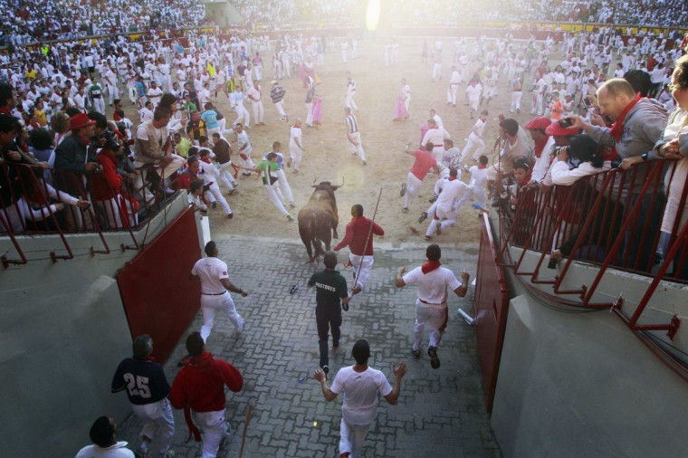 Runners lead an Alcurrucen fighting bull into the bull ring during the first running of the bulls of the San Fermin festival in Pamplona. (Joseba Etxaburu/Reuters photo)