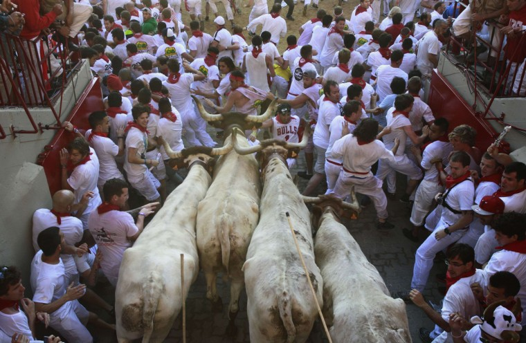 Steers make their way through a crowd of runners at the entrance to the bull ring during the first running of the bulls of the San Fermin festival in Pamplona. (Joseba Etxaburu/Reuters photo)