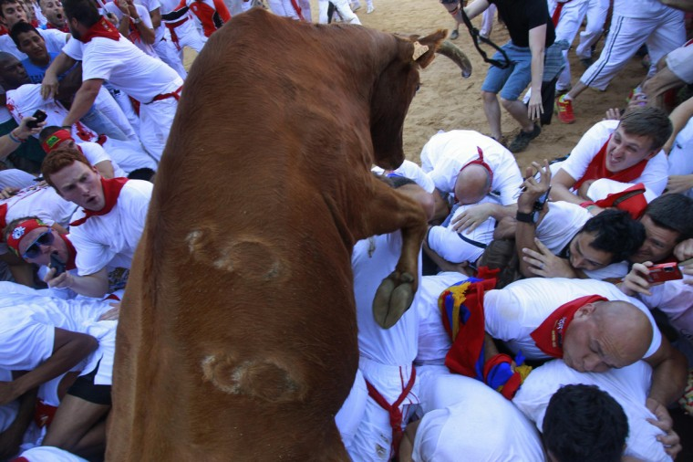 A fighting cow leaps over revellers upon entering the bullring following the first running of the bulls of the San Fermin festival in Pamplona. (Joseba Etxaburu/Reuters photo)
