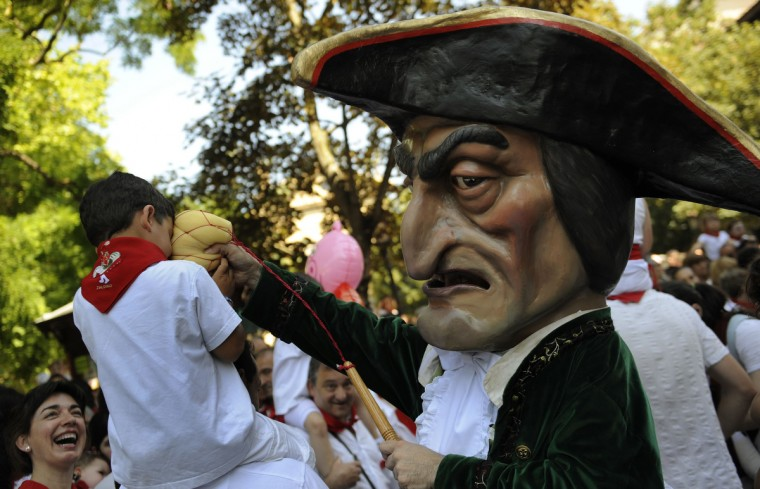 "A ""Kiliki"" hits a child in his face with a sponge at the San Fermin festival in Pamplona. ""Kilikis"", wearing outsized masks and playfully hitting bystanders with sponges on sticks, parade daily through the city accompanied by brass bands during the nine-day-long festival made popular by U.S. writer Ernest Hemingway. (Eloy Alonso/Reuters photo)"
