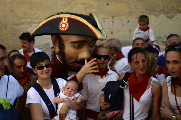 "A ""Kiliki"" gestures next to crowds during San Fermin day at the San Fermin festival in Pamplona. ""Kilikis"", wearing outsized masks and playfully hitting bystanders with sponges on sticks, parade daily through the city accompanied by brass bands during the nine-day-long festival. (Vincent West/Reuters photo)"