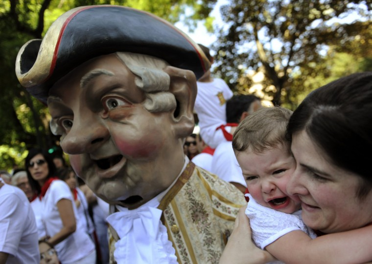 "A child cries next to a ""Kiliki"" at the San Fermin festival in Pamplona. ""Kilikis"", wearing outsized masks and playfully hitting bystanders with sponges on sticks, parade daily through the city accompanied by brass bands during the nine-day-long festival. (Eloy Alonso/Reuters photo)"