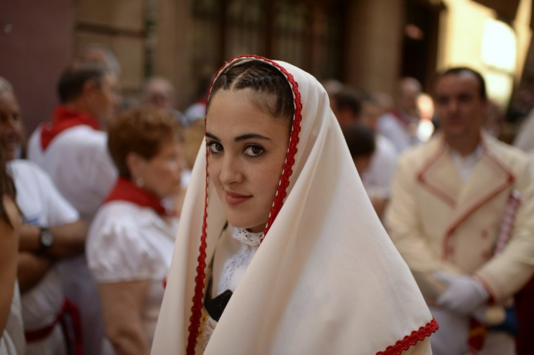 A woman smiles as she takes part in a parade on San Fermin day in Pamplona. San Fermin is the patron saint of the nine day annual festival. (Vincent West/Reuters photo)