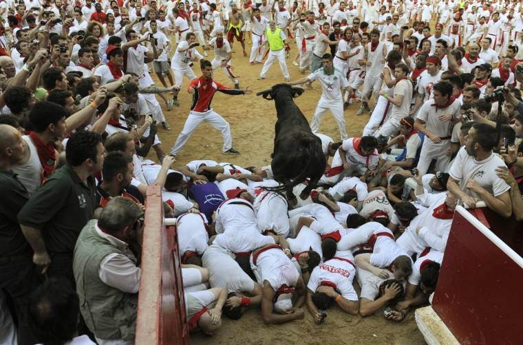 A fighting cow leaps over revellers upon entering the bullring following the second running of the bulls of the San Fermin festival in Pamplona. (Eloy Alonso/Reuters photo)