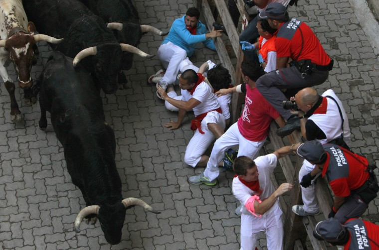 Runners fall next to Valdefresno fighting bulls at the entrance to the bullring during the third running of the bulls of the San Fermin festival in Pamplona. (Joseba Extaburu/Reuters photo)