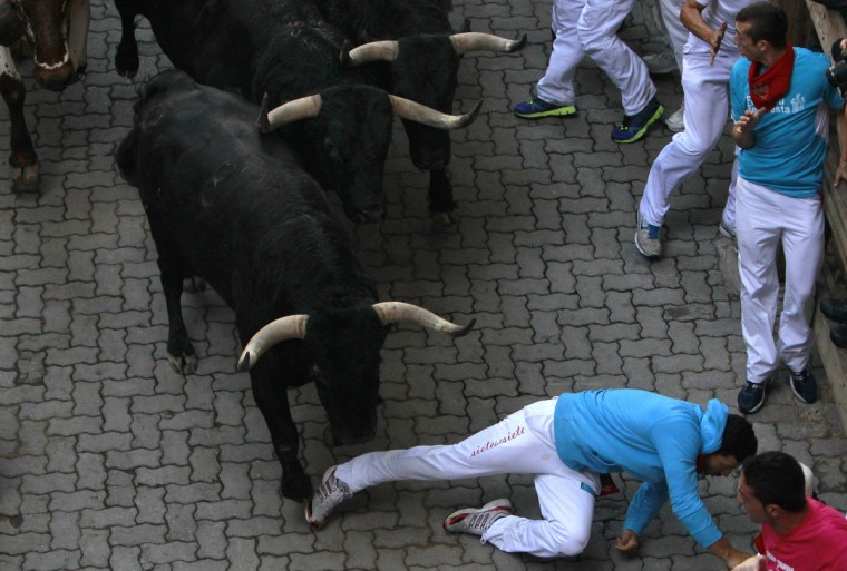 A runner is knocked down by Valdefresno fighting bulls at the entrance to the bullring during the third running of the bulls of the San Fermin festival in Pamplona. (Joseba Extaburu/Reuters photo)