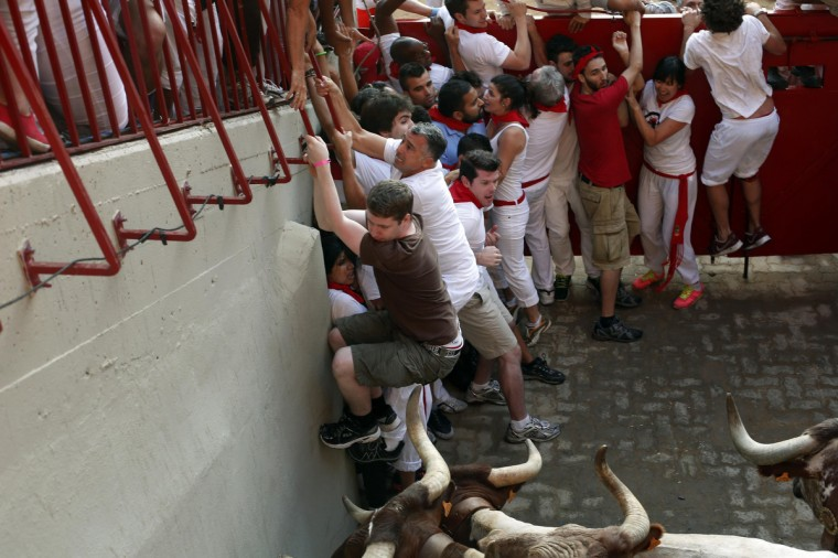 Runners get trapped by steers at the entrance to the bull ring during the third running of the bulls at the San Fermin festival in Pamplona. (Susana Vera/Reuters photo)