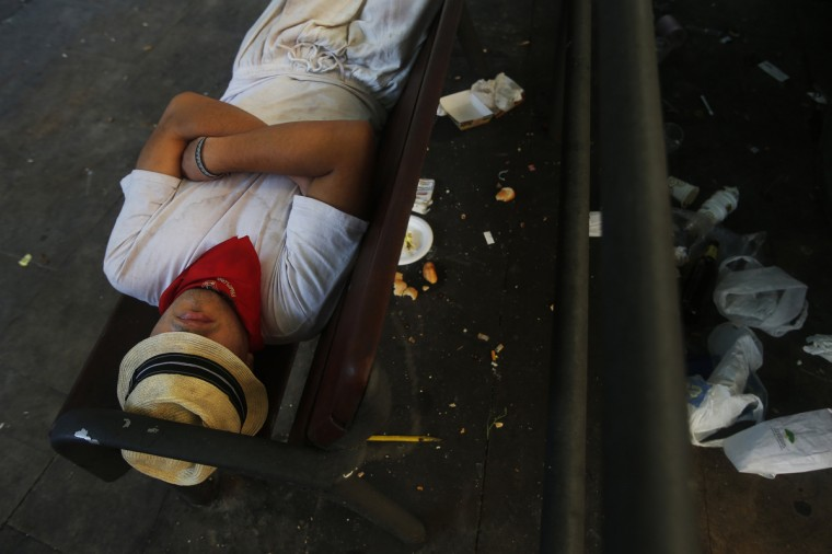 A reveller sleeps on a public bench after the second running of the bulls of the San Fermin festival in Pamplona. (Susana Vera/Reuters photo)
