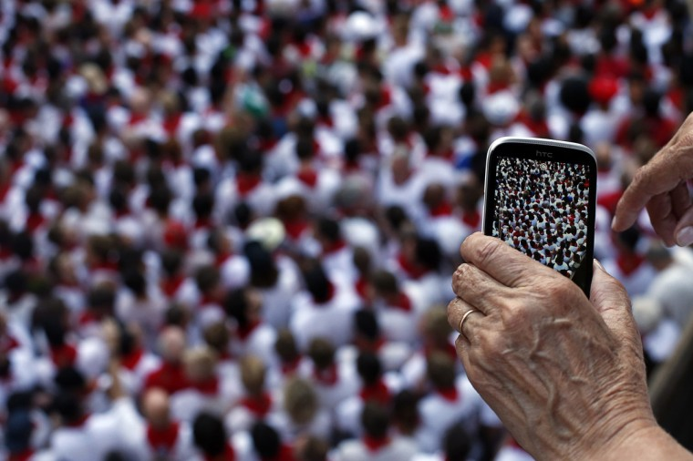 A woman uses her smart phone on a balcony to record the runners waiting for the start of the second running of the bulls of the San Fermin festival in Pamplona. (Susana Vera/Reuters photo)