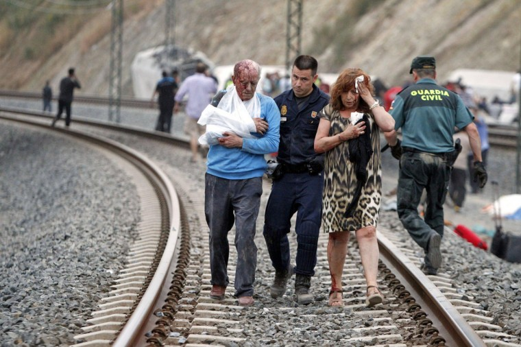 Victims are helped by rescue workers after a train crashed near Santiago de Compostela, northwestern Spain, July 24, 2013. At least 56 people died after a train derailed in the outskirts of the northern Spanish city of Santiago de Compostela, the head of Spain's Galicia region, Alberto Nunez Feijoo, told Television de Galicia. (Monica Ferreiros/La Voz de Galicia/via Reuters)