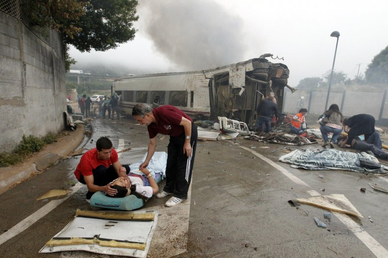 Victims receive help after a train crashed near Santiago de Compostela, northwestern Spain, July 24, 2013. At least 56 people died after a train derailed in the outskirts of the northern Spanish city of Santiago de Compostela, the head of Spain's Galicia region, Alberto Nunez Feijoo, told Television de Galicia. (Monica Ferreiros/La Voz de Galicia/via Reuters)