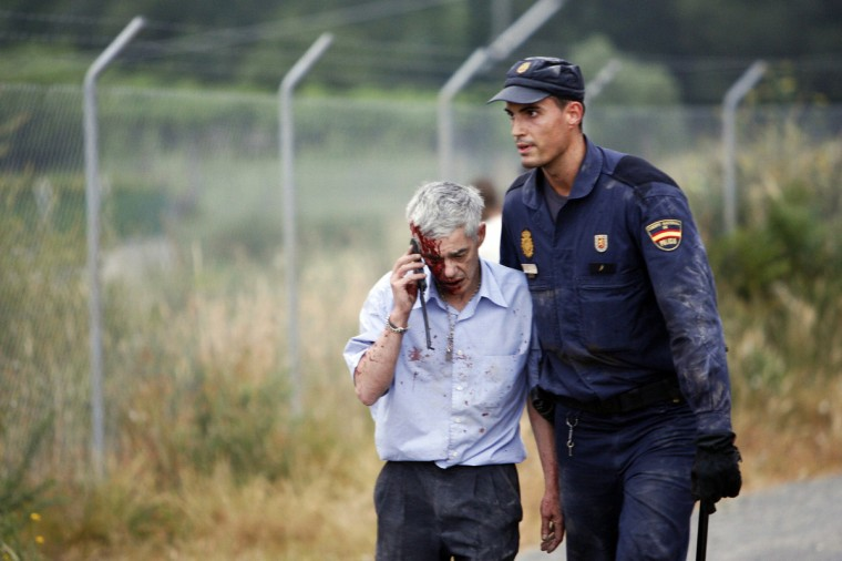 An injured passenger is helped by a policeman after a train crashed near Santiago de Compostela, northwestern Spain, July 24, 2013. At least 35 people died after a train derailed in the outskirts of the northern Spanish city of Santiago de Compostela, the head of Spain's Galicia region, Alberto Nunez Feijoo, told Cadena Ser radio on Wednesday. A woman who was close to the site of the accident told the radio station that she had first heard a loud explosion and then seen the train derailed. (Oscar Corral/Reuters photo)