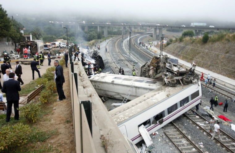 Rescue workers pull victims from a train crash near Santiago de Compostela, northwestern Spain, July 24, 2013. At least 35 people were killed and 50 injured when a train derailed on the outskirts of the northern Spanish city of Santiago de Compostela on Wednesday in one of the country's worst rail disasters. Bodies covered in blankets lay next to carriages as smoke billowed from the wreckage a few hundred meters away from the entrance to the city's main station. (Oscar Corral/Reuters photo)