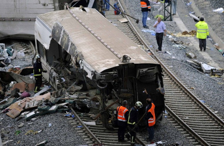 Rescue workers inspect the wreckage of a train crash near Santiago de Compostela, northwestern Spain, early July 25, 2013. A train derailed outside the ancient northwestern Spanish city of Santiago de Compostela on Wednesday evening, killing at least 77 people and injuring up to 131 in one of Europe's worst rail disasters. (Eloy Alonso/Reuters photo)