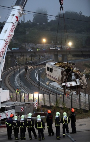 Firefighters watch as a crane removes a carriage from the tracks at the site of a train crash near near Santiago de Compostela, northwestern Spain, July 25, 2013. A train derailed outside the ancient northwestern Spanish city of Santiago de Compostela on Wednesday evening, killing at least 77 people and injuring up to 131 in one of Europe's worst rail disasters. (Miguel Vidal/Reuters photo)