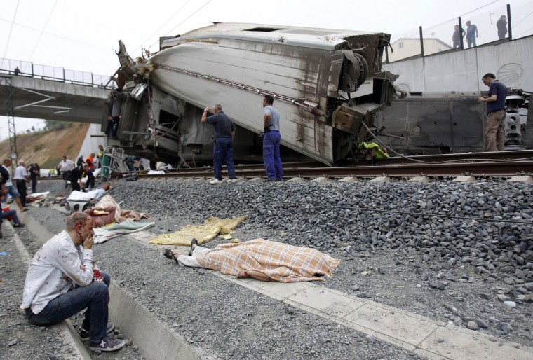 A wounded victim sits next to a body covered with a blanket after a train crashed near Santiago de Compostela, northwestern Spain, July 24, 2013. At least 56 people died after a train derailed in the outskirts of the northern Spanish city of Santiago de Compostela, the head of Spain's Galicia region, Alberto Nunez Feijoo, told Television de Galicia. (Monica Ferreiros/La Voz de Galicia/via Reuters)