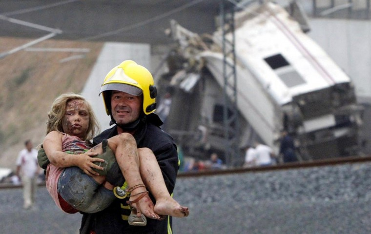 A fireman carries a wounded victim from the wreckage of a train crash near Santiago de Compostela, northwestern Spain, July 24, 2013. A train derailed outside the ancient northwestern Spanish city of Santiago de Compostela on Wednesday evening, killing at least 77 people and injuring up to 131 in one of Europe's worst rail disasters. (Xoan A. Soler/Monica Ferreiros -- La Voz de Galicia via Reuters)