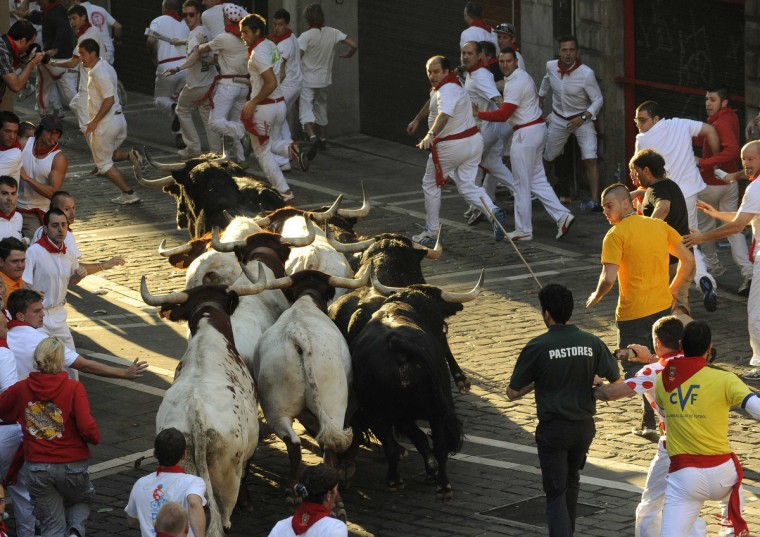 Runners sprint in front of Valdefresno fighting bulls on Santo Domingo hill during the third running of the bulls of the San Fermin festival in Pamplona. (Eloy Alonso/Reuters photo)