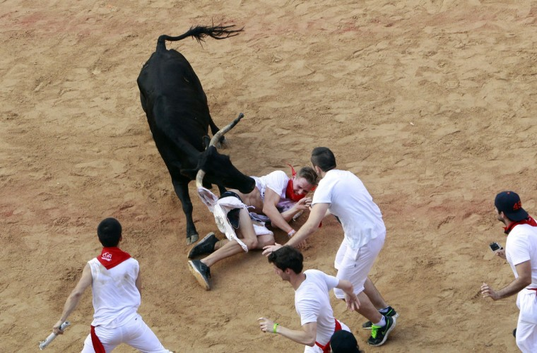 A wild cow rips the pants of a reveler after the fifth running of the bulls of the San Fermin festival in Pamplona. (Joseba Etxaburu/Reuters)