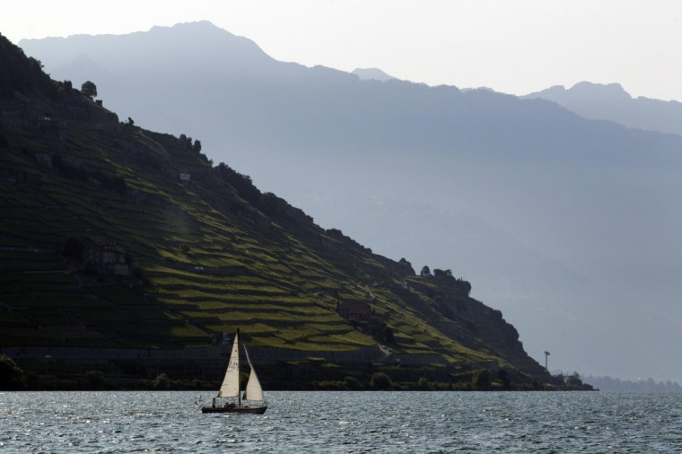 A boat sails out of Cully harbour on Lake Leman in front of the UNSECO listed Lavaux vineyards on a summer morning. (Denis Balibouse/Reuters photo)