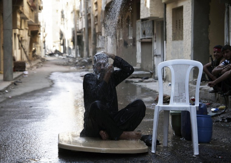 A Free Syrian Army fighter takes a shower while wearing his clothes, calling on other fellows to do the same to avoid being surprised by enemies in Deir al-Zor. (Khalil Ashawi/Reuters photo)