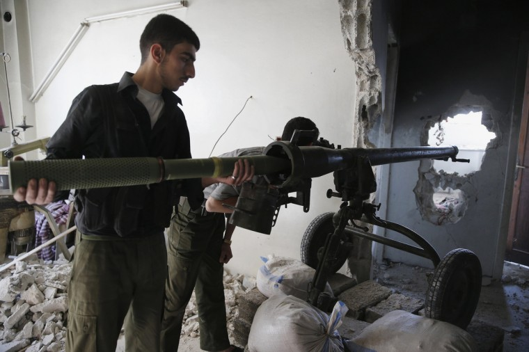 A Free Syrian Army fighter positions a cannon inside a house in Jobar, Damascus. (Mohamed Abdullah/Reuters)