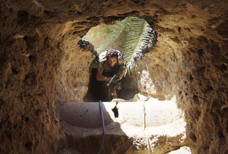 A Free Syrian Army fighter moves through a tunnel to take cover from snipers loyal to Syria's President Bashar al-Assad in Deir al-Zor July 14, 2013. Picture taken July 14, 2013. (Khalil Ashawi/Reuters)