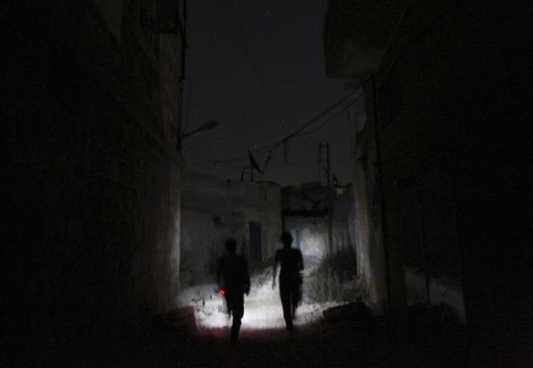 Free Syrian Army fighters move along a street at night in Aleppo's Karm al-Jabal district July 15, 2013. Picture taken July 15, 2013. (Muzaffar Salman/Reuters)