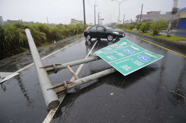A damaged street sign blocks a road after it was blown over by strong winds from Typhoon Soulik, in Ilan County, July 13, 2013. Typhoon Soulik brought powerful winds and heavy rain as it landed in Taiwan early Saturday, killing one and injuring 21, local media said. (Tony Huang/Reuters)