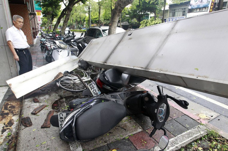 A man inspects motorcycles damaged by a fallen shop sign after strong winds and rain from Typhoon Soulik hit Taipei July 13, 2013. Typhoon Soulik brought powerful winds and heavy rain as it landed in Taiwan early Saturday, killing one and injuring 21, local media said. (Pichi Chuang/Reuters)