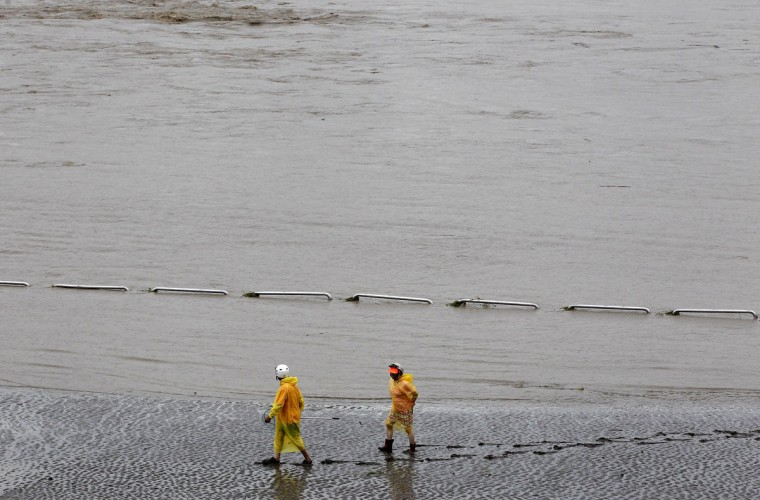 People wearing ponchos walk along a flooded river near Sioulang Bridge, as Typhoon Soulik hits New Taipei City July 13, 2013. Typhoon Soulik brought powerful winds and heavy rain as it landed in Taiwan early Saturday, killing one, injuring 21 and causing flash floods, local media said. (Pichi Chuang/Reuters)