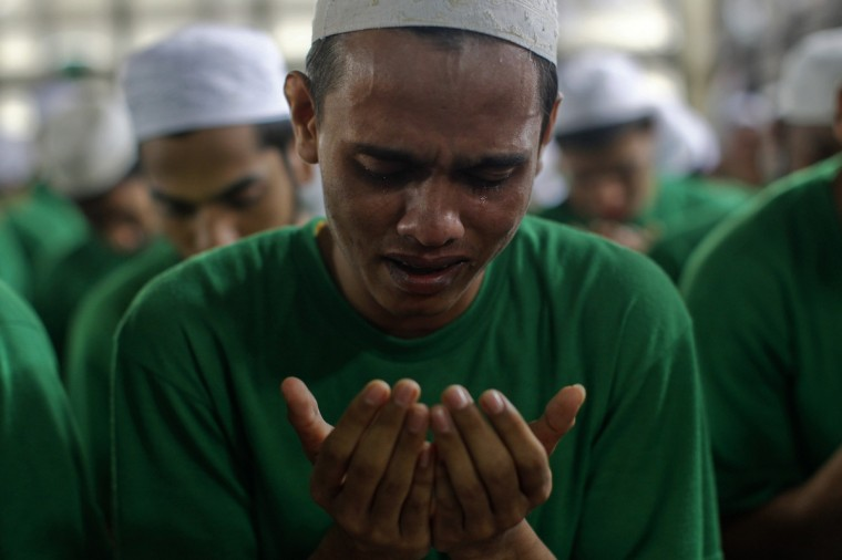 A Rohingya Muslim illegal immigrant cries as he prays at the Immigration Detention Centre during the Muslim holy fasting month of Ramadan in Kanchanaburi province July 10, 2013. More than a hundred Rohingya Muslims gathered to pray and break fast as they welcome the first day of Ramadan in Thailand. The stateless people arrived in Thailand earlier in January this year after fleeing a bloody conflict between the Buddhist and Muslims in Myanmar's western Rakhine State. (Athit Perewongmetha/Reuters)