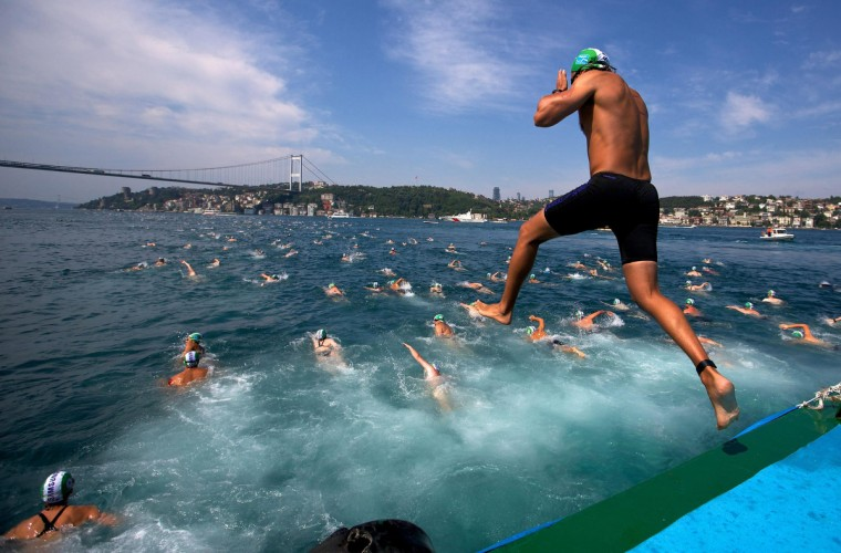 A competitors jumps into the water to swim from Asia to Europe during the annual Bosphorus Cross-Continental swimming competition in Istanbul. Few stretches of water in the world can match the mix of physical challenge and sheer emotional exhilaration that the Bosphorus Strait offers to swimmers making the legendary crossing from Asia to Europe. Competitors in Istanbul's annual Bosphorus Cross-Continental can ponder stunning Ottoman palaces, modern suspension bridges and 500-year-old military fortresses as they navigate currents first celebrated in ancient Greek myths. (Cevahir Bugu/Reuters)