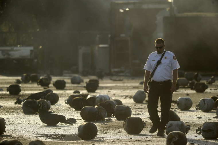 Tavares Fire Battalion Chief Jeff Hosterman walks among the remains of exploded propane cylinders, littering the storage yard of a propane plant, after massive explosions overnight in the plant's yard, in Tavares, Florida. Dozens of explosions rocked a propane tank servicing plant in central Florida, northwest of Orlando, late on Monday, injuring seven workers, at least three critically, and prompting the evacuation of nearby homes, authorities said. (David Manning/Reuters)