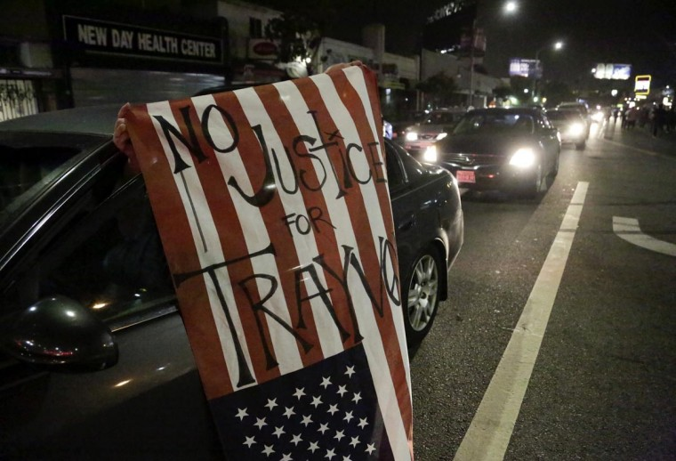 "A driver on Crenshaw Boulevard holds an American flag with the words ""No justice for Trayvon,"" following the George Zimmerman verdict, in Los Angeles, California July 13, 2013. (Jason Redmond/Reuters)"