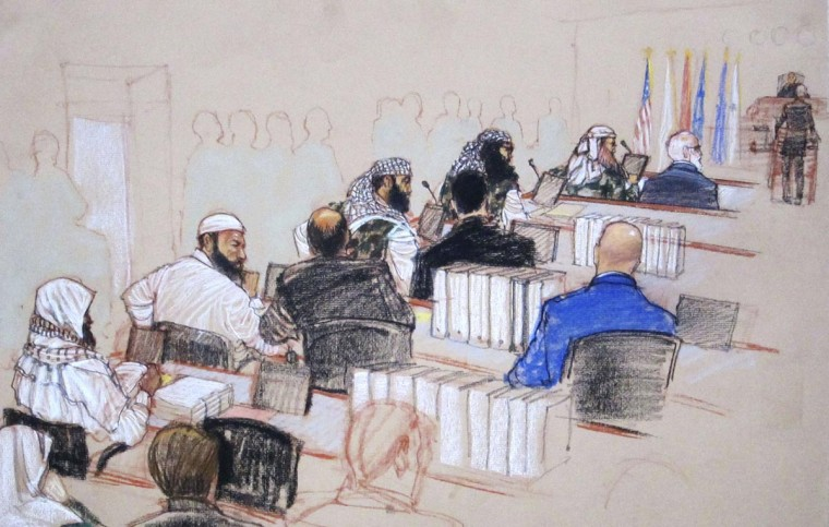 (L-R, wearing camouflage) Ramzi, Walid bin Attash and Khalid Sheikh Mohammad, three of the alleged conspirators in the 9/11 attacks, attend court dressed in camouflage during hearings in Guantanamo Bay, Cuba January 28, 2013 in this Pentagon-approved court sketch. Defense lawyer Cheryl Bormann, in hijab, stands at the podium before presiding judge Army Colonel James Pohl. (Janet Hamlin/Reuters)