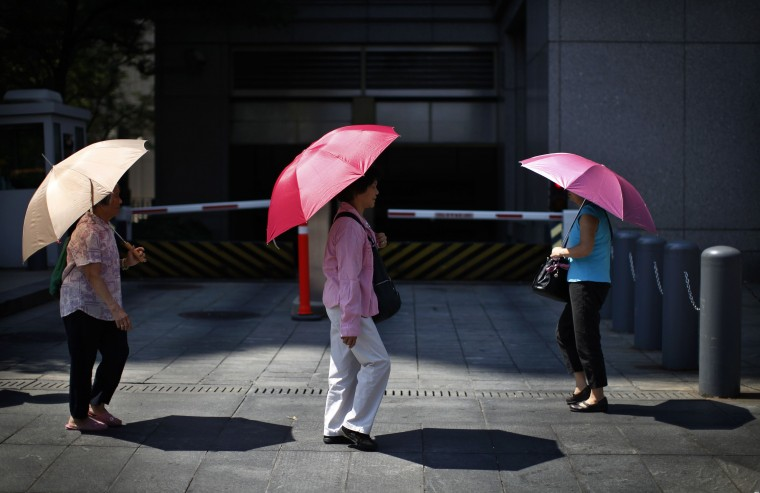 Women shield themselves from the midday sun with umbrellas, in the Chinatown section of lower Manhattan in New York City. Temperatures in New York City, the nation's biggest metropolitan area, soared into the upper 90s Fahrenheit for a fourth straight day. (Mike Segar/Reuters photo)