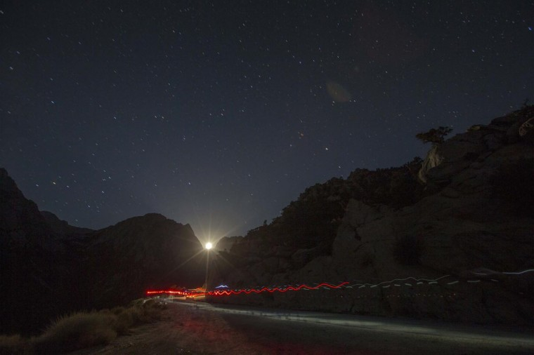 A trail of headlamps is seen as runners make their way to the finish line in the Badwater Ultramarathon at the foot of Mount Whitney, California July 16, 2013. (Lucy Nicholson/Reuters)