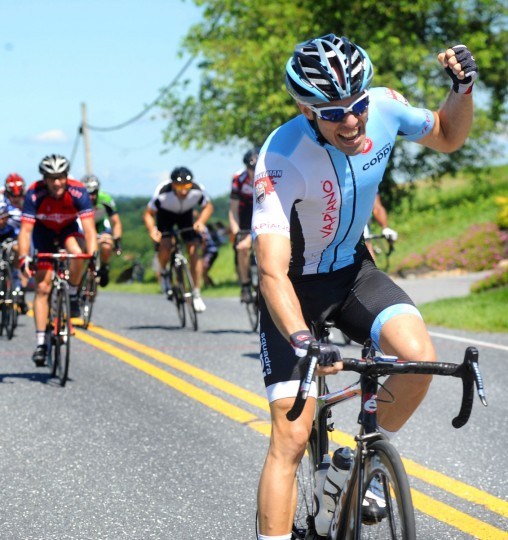 Michael Russo of Arlington, Virginia celebrates as he crosses the finish line to win the CAT 4 division of the Road Warrior 50 road race. (Jerry Jackson/Baltimore Sun)