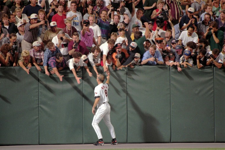 Fans reach out to Cal Ripken Jr. on Sept. 6, 1995 as he runs around the field at Camden Yards after he broke Lou Gehrig's record for consecutive games played. (Gene Sweeney Jr. / The Baltimore Sun)