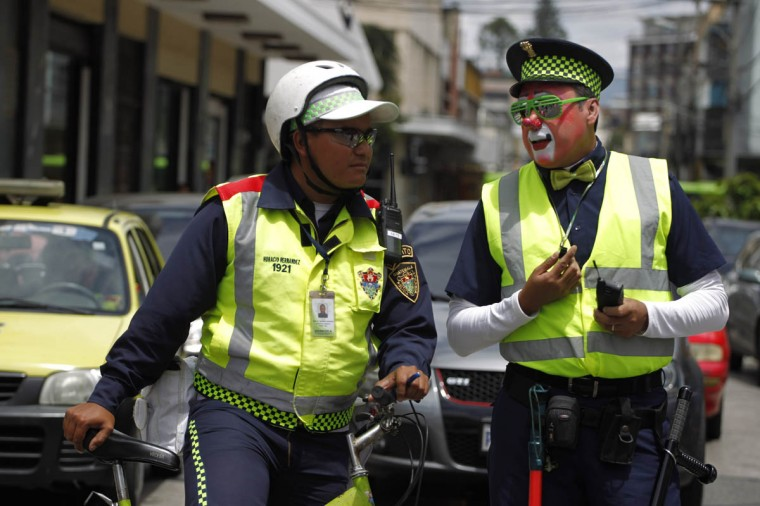 A transit police agent is spoken to by a clown (Right) dressed like him during a parade to inaugurate the 5th Annual Clowns' Convention in Guatemala City. According to the organizers, the convention sees participants coming from Mexico and Central America. (Jorge Dan Lopez/Reuters photo)