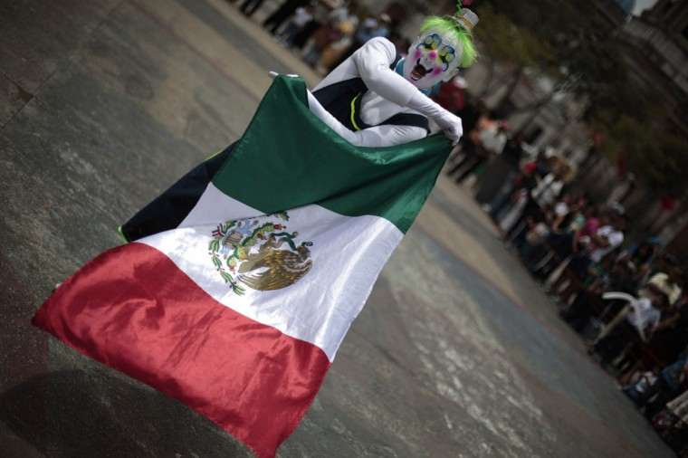 A clown holds a Mexican Flag during a parade to inaugurate the 5th Annual Clowns' Convention in Guatemala City. (Jorge Dan Lopez/Reuters photo)