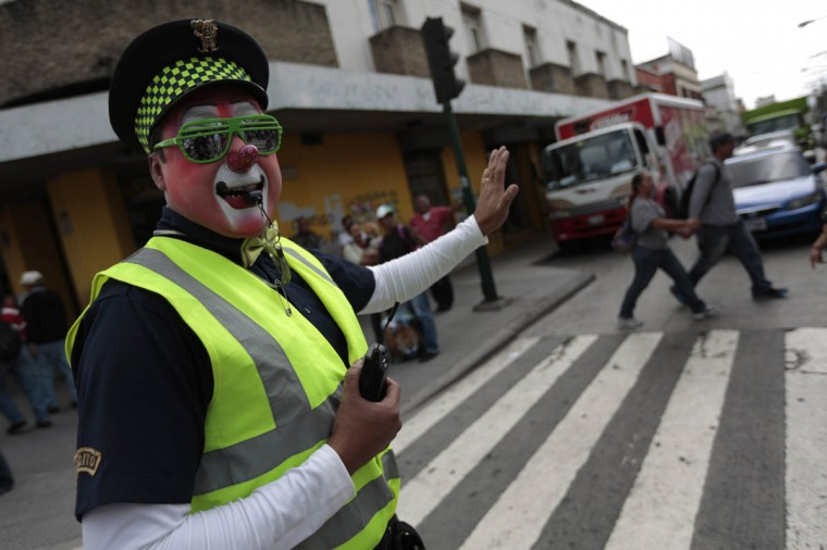 A clown dressed as a transit police agent directs traffic during a parade to inaugurate the 5th Annual Clowns' Convention in Guatemala City, July 23, 2013. According to the organizers, the convention sees participants coming from Mexico and Central America. (Jorge Dan Lopez/Reuters photo)