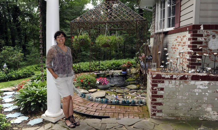 Artist Sherrill Cooper stands on her porch with the koi pond in the background. (Barbara Haddock Taylor/Baltimore Sun)