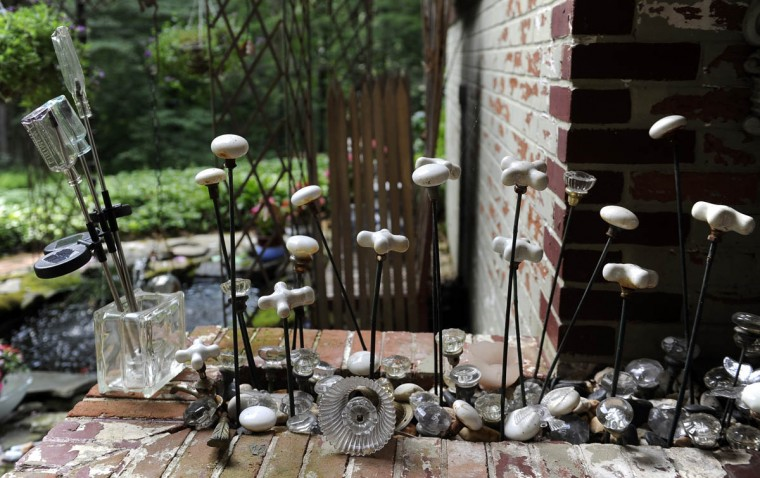 This is a display of porcelain doorknobs that look like flowers in the garden of artist Sherrill Cooper. (Barbara Haddock Taylor/Baltimore Sun)