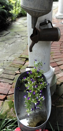 This is a decoration on a pillar in the garden. Water drips from an air conditioner and falls through the watering cans into the flower pot. (Barbara Haddock Taylor/Baltimore Sun)